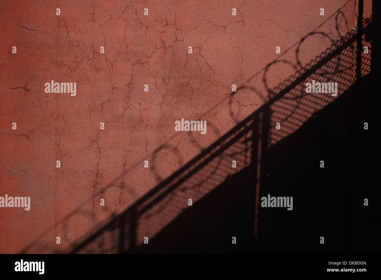 The shadow of a barbed wire fence against an old cracked wall. - Stock Image