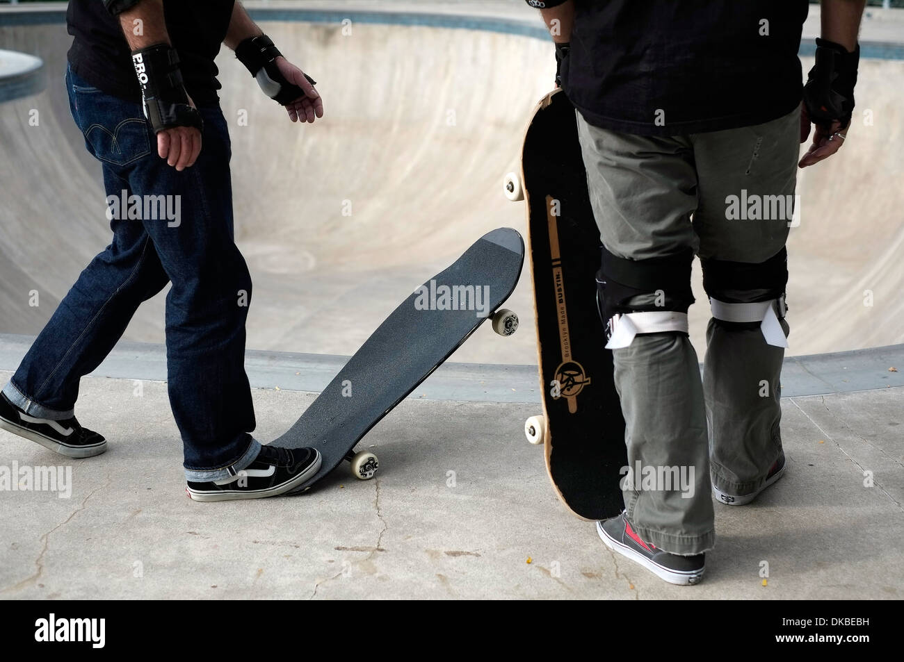 Two skateboarders prepare to ride in the bowl at the Chelsea Skatepark in Manhattan, New York City. - Stock Image