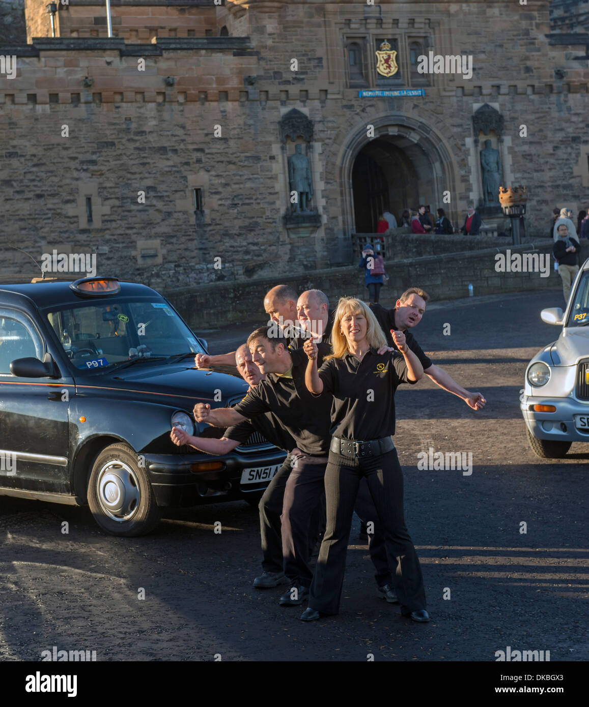 Cabbies from the Central Taxi company in Edinburgh, Scotland, dance for a company tv advertisement in front of castle. Stock Photo