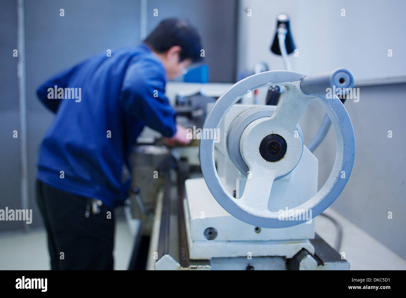 Worker at small parts manufacturing factory in China Stock Photo