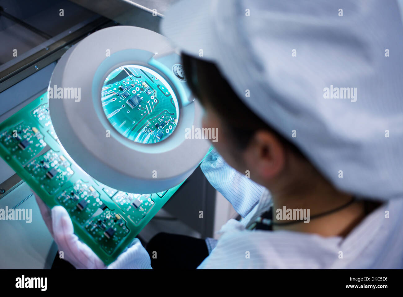 Worker at small parts manufacturing factory in China looking through magnifier at microchips - Stock Image