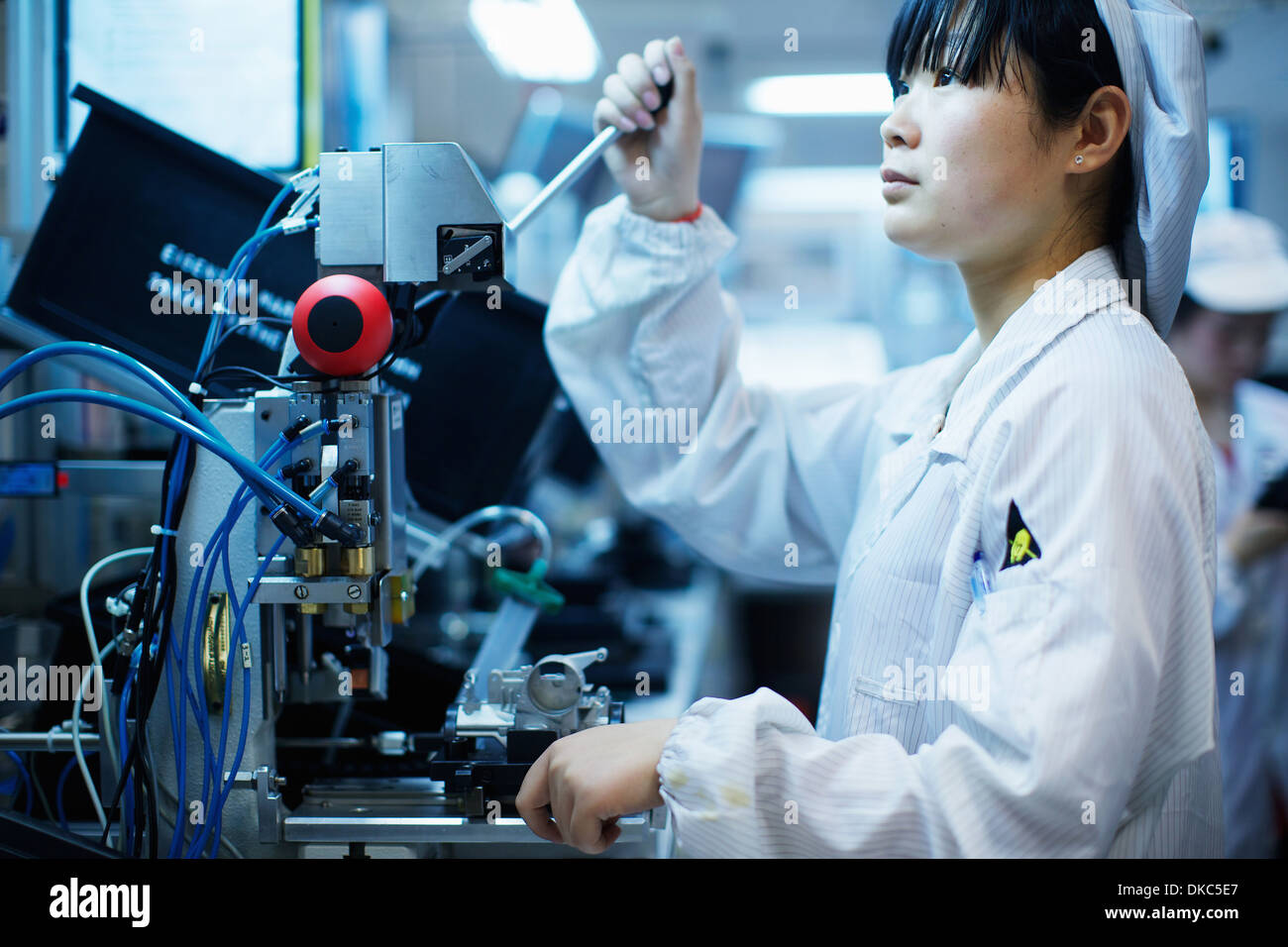 Worker at small parts manufacturing factory in China - Stock Image