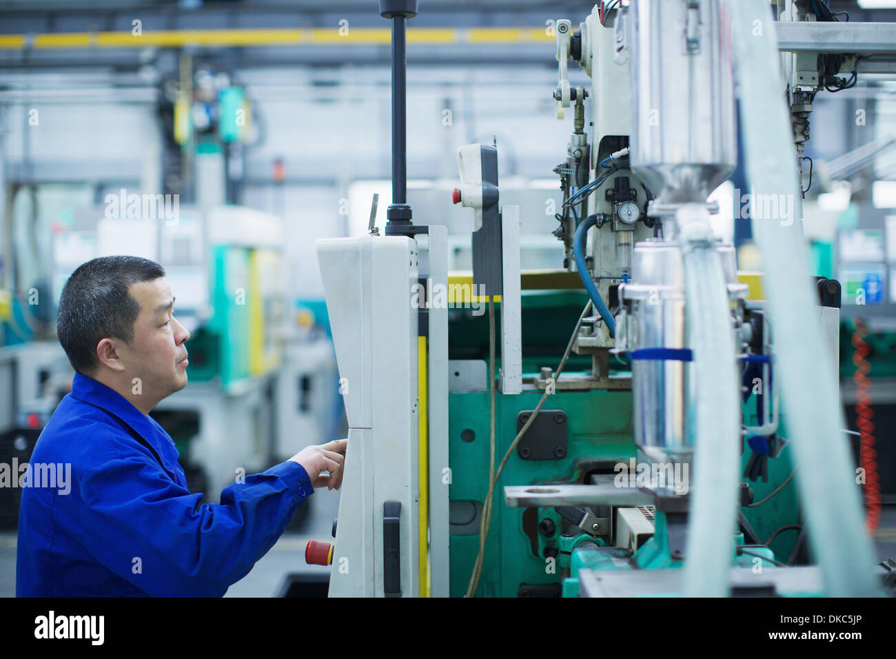 Worker at small parts manufacturing factory in China, pressing button on control panel - Stock Image
