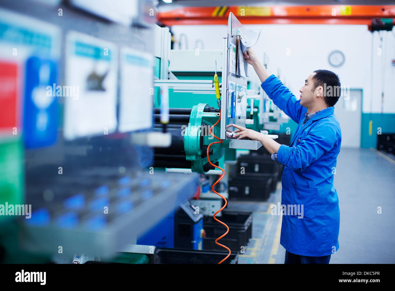 Worker at small parts manufacturing factory in China, reaching up to press button on control panel Stock Photo