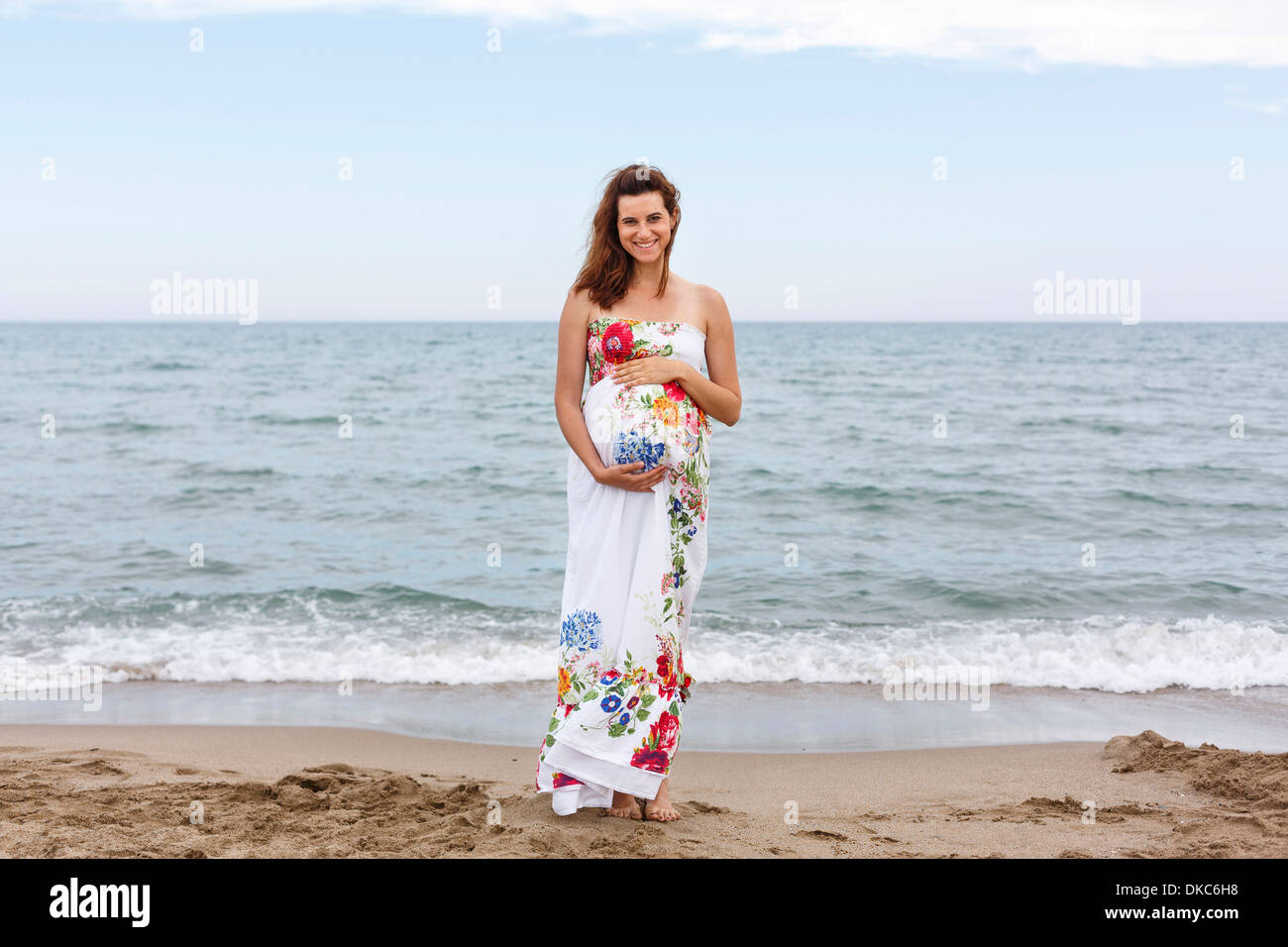 Pregnant woman standing on beach, hands on stomach - Stock Image