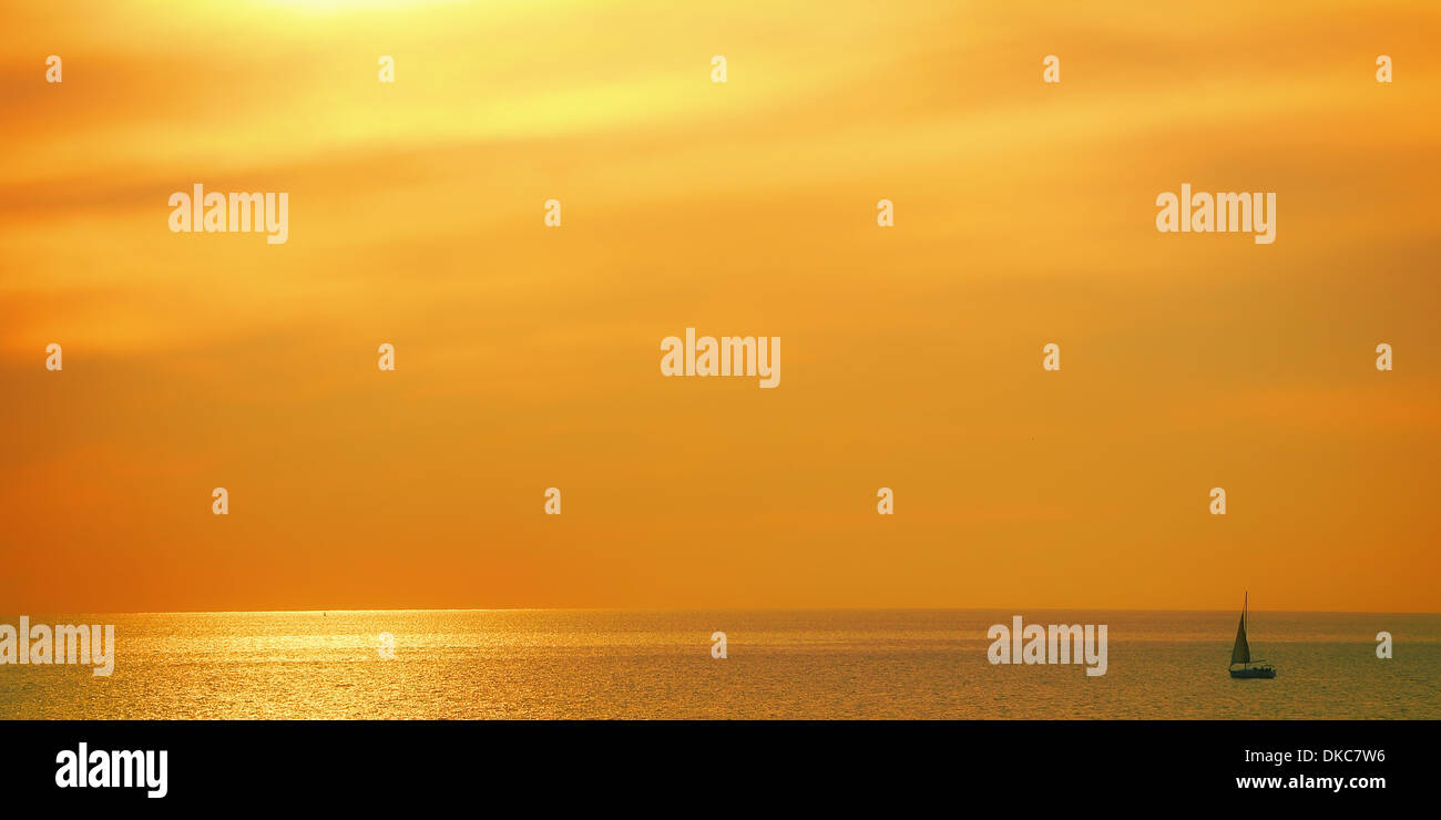 Ship sinking in the golden sunset in the Mediterranean Sea - Stock Image