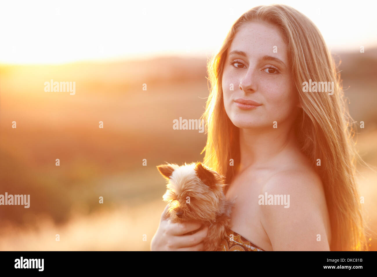 Teenager standing in field at dusk holding domestic dog - Stock Image