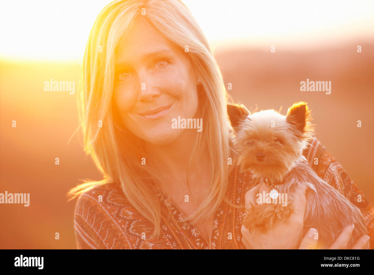 Woman standing in field at dusk holding domestic dog - Stock Image