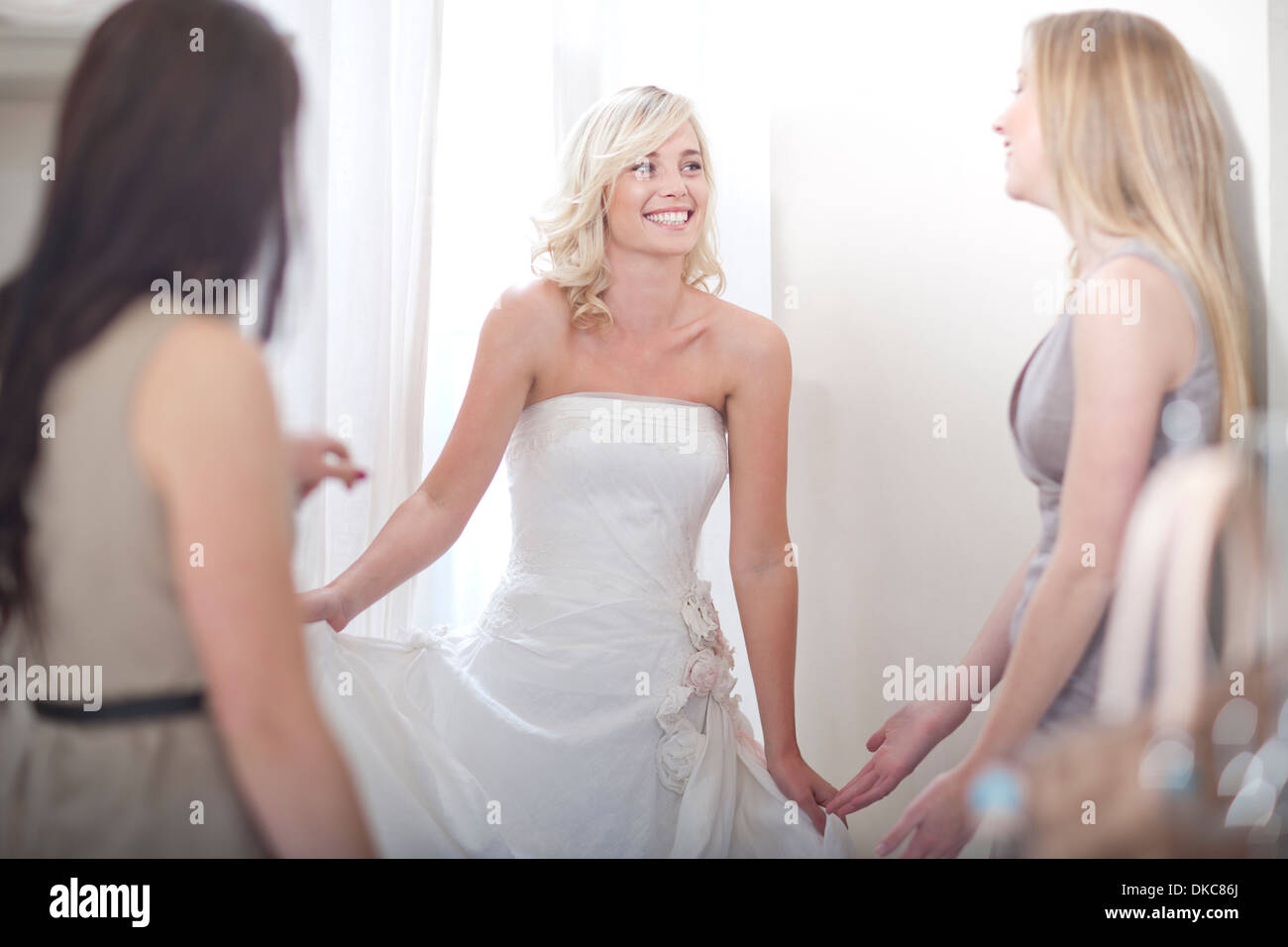 Young woman trying on wedding dress, with friends - Stock Image