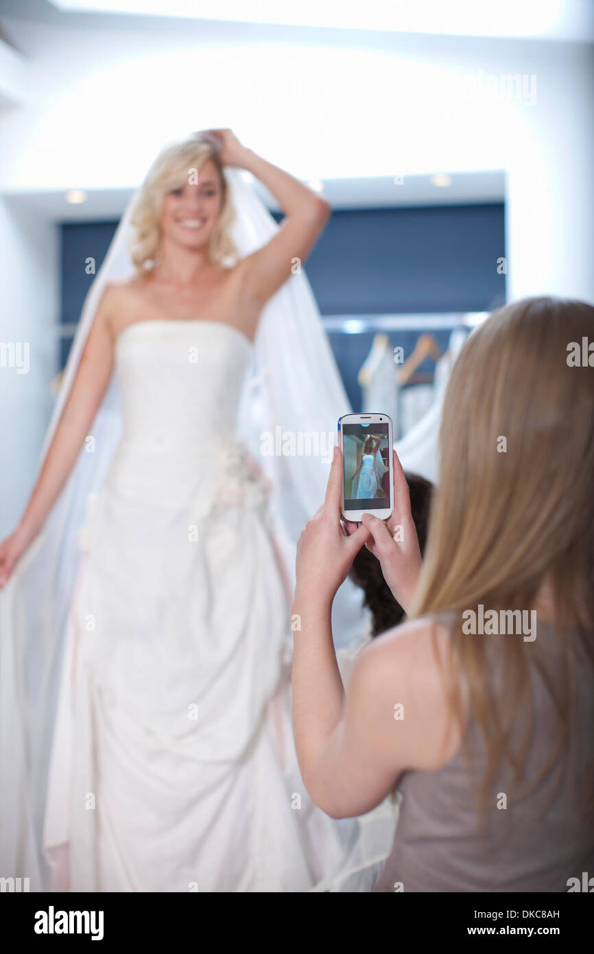 Young woman taking photograph of friend trying on wedding dress - Stock Image