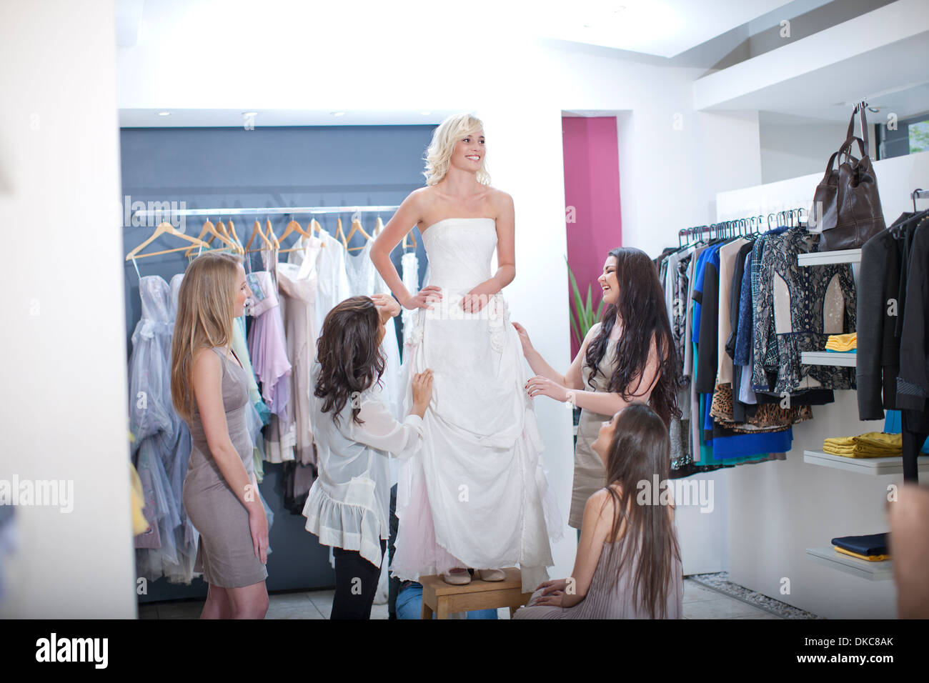 Young woman trying on wedding dress, with friends Stock Photo