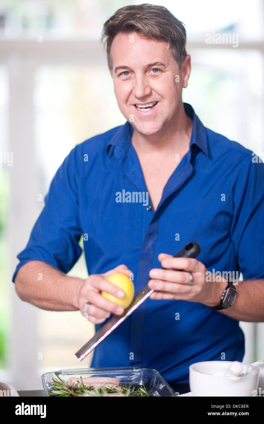 Mature man grating lemon zest - Stock Image