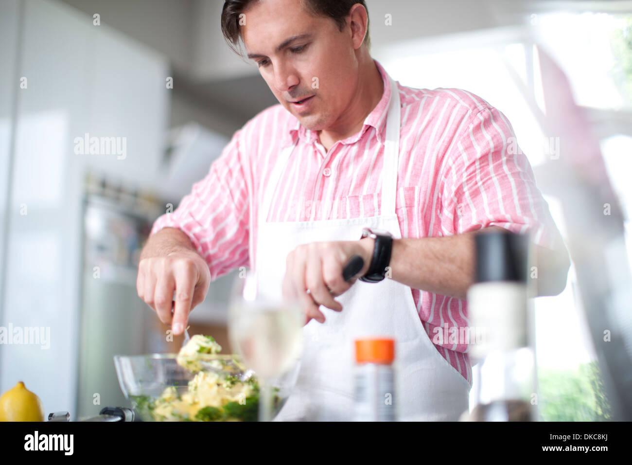 Mature men cooking, mixing ingredients in bowl - Stock Image
