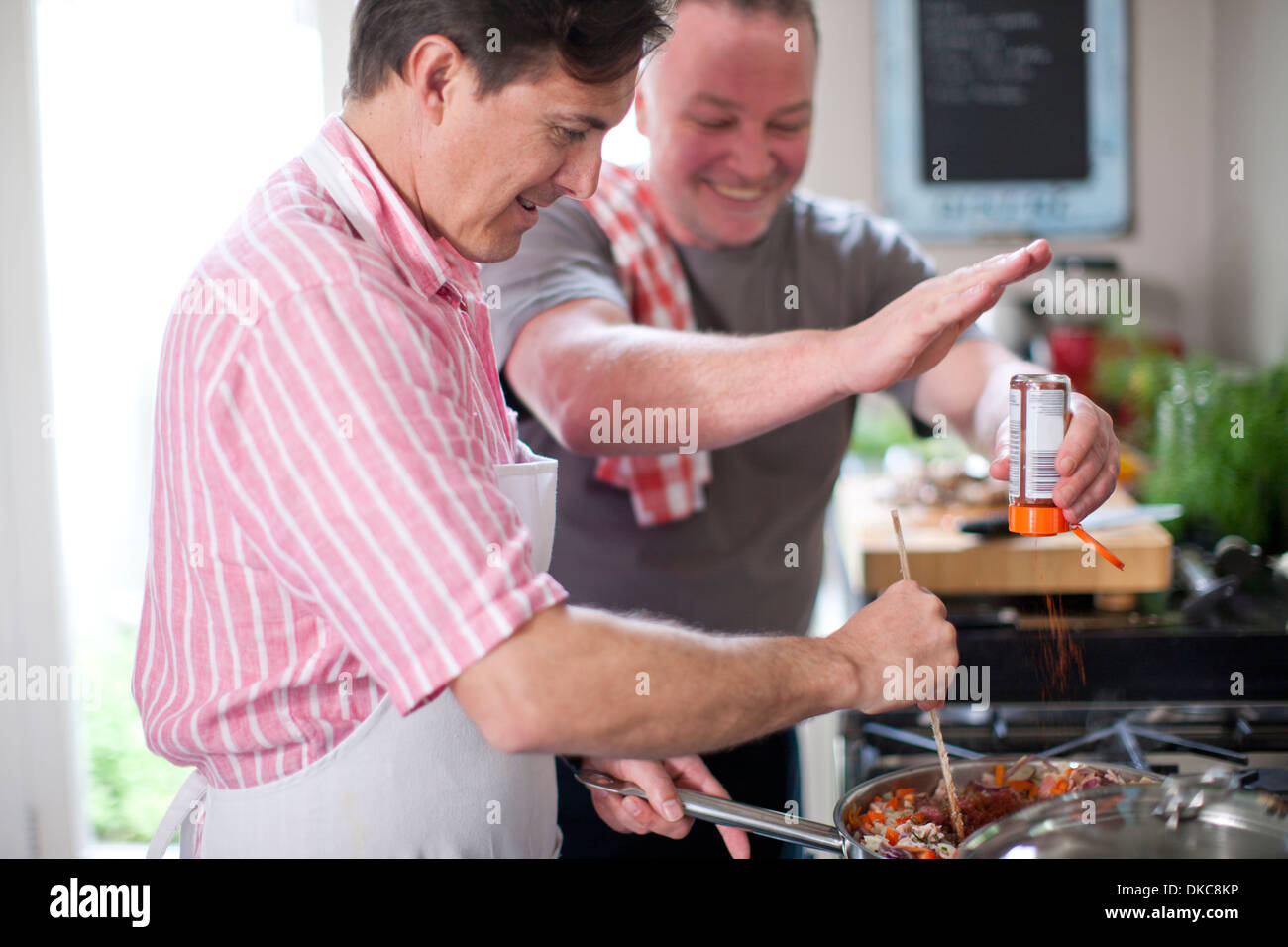 Mature men cooking, one stirring and one adding spices - Stock Image