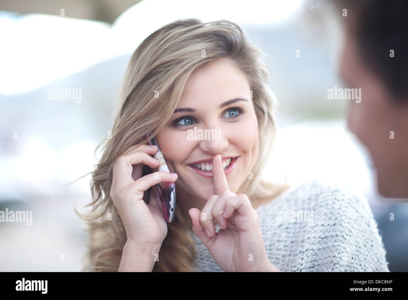 Young woman on phonecall with finger to lips - Stock Image