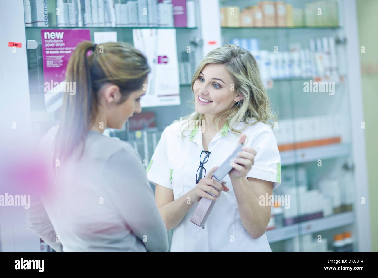 Pharmacist showing customer box of medication - Stock Image