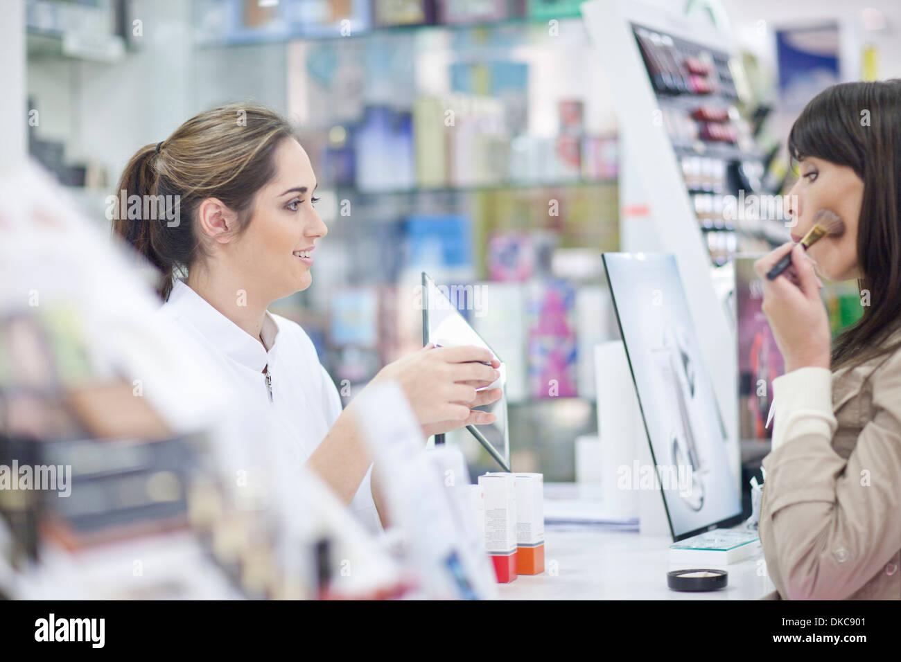 Shop assistant doing make up demonstration - Stock Image