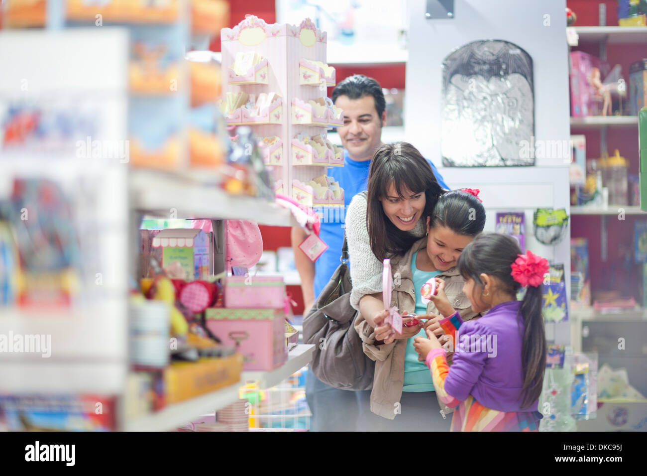 Family with two daughters shopping in toy shop - Stock Image