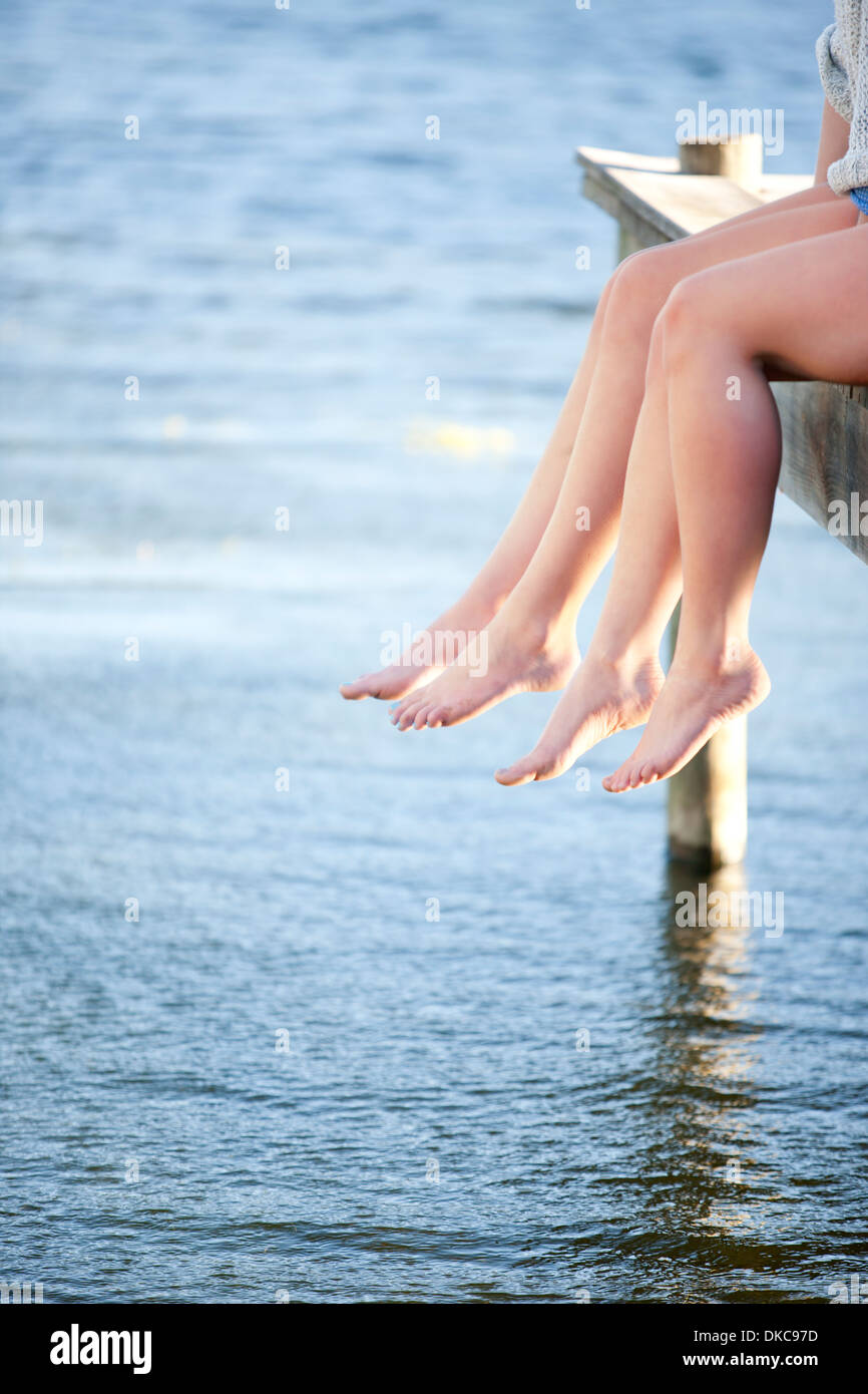 Two pairs of female legs dangling from pier - Stock Image