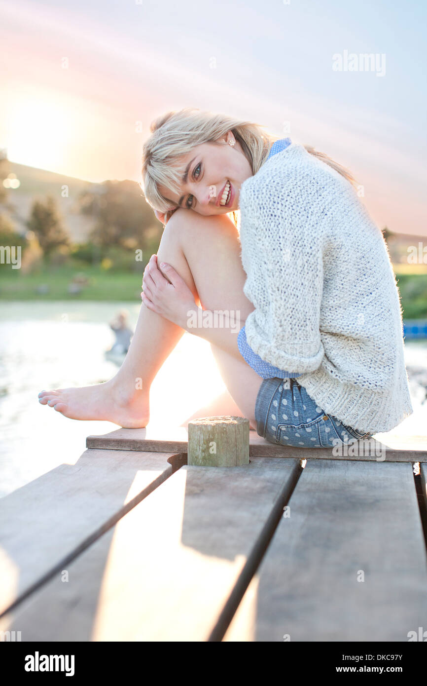 Shy young woman sitting on pier - Stock Image