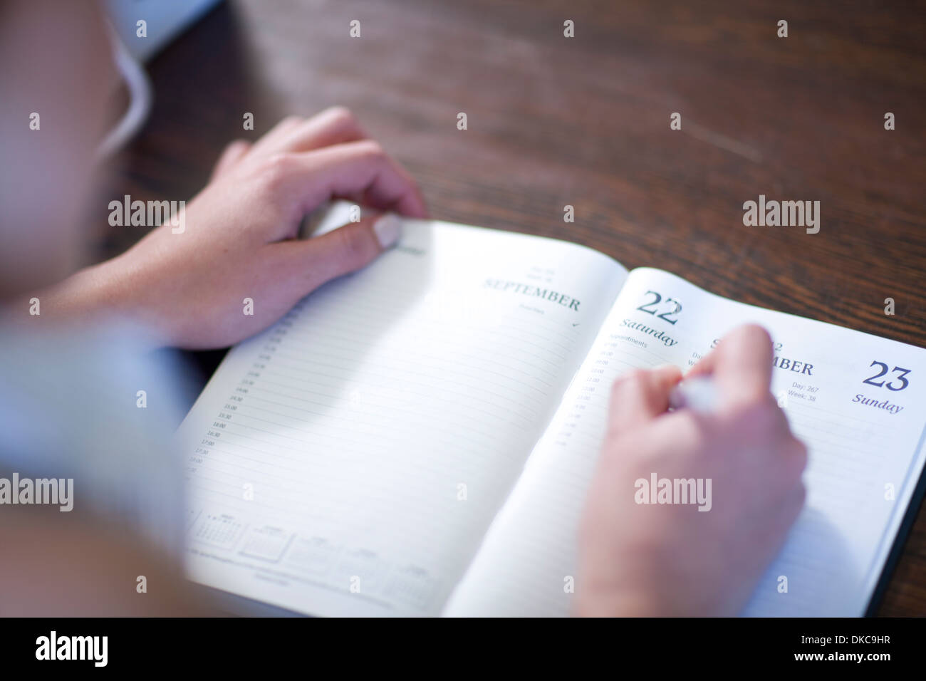 Close up of female writing in diary - Stock Image