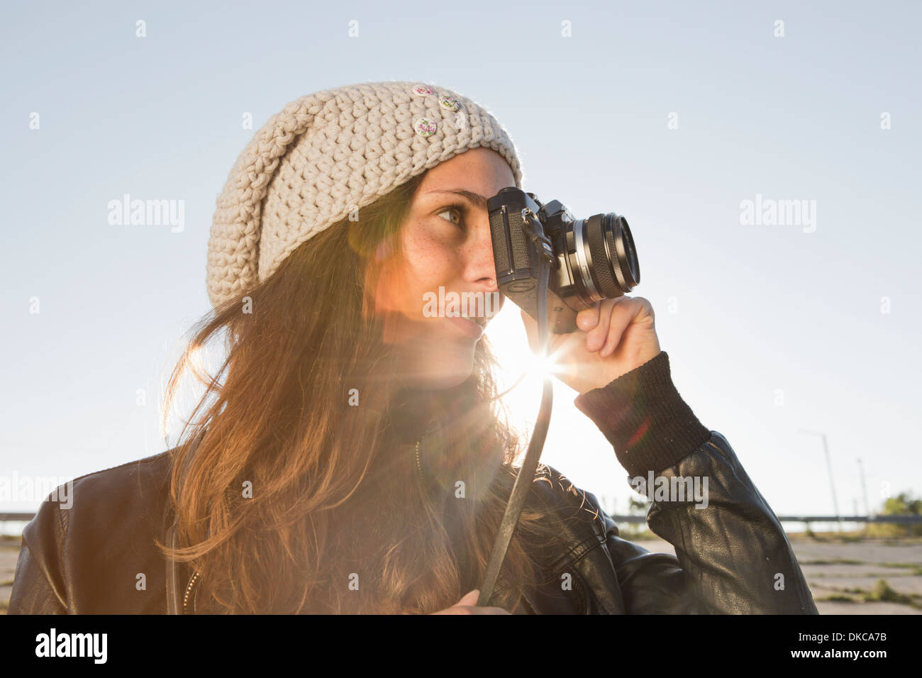 Portrait of young woman using slr camera - Stock Image