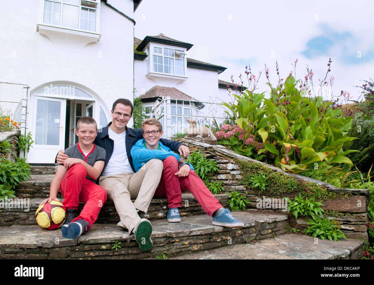 Father and sons sitting on steps in garden Stock Photo