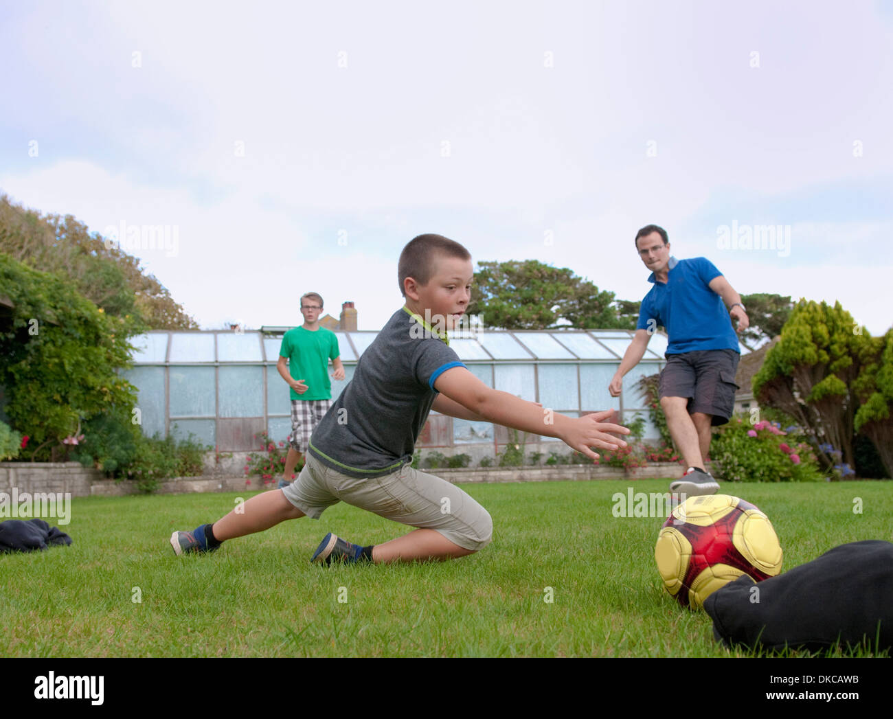 Father and sons playing football in garden - Stock Image
