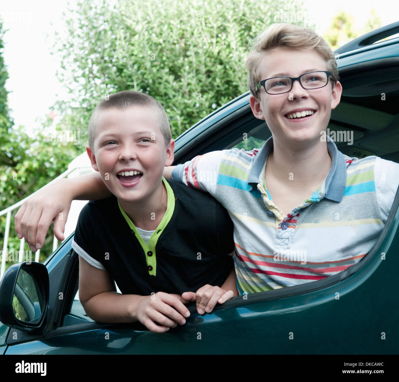 Portrait of two brothers leaning out of car window - Stock Image