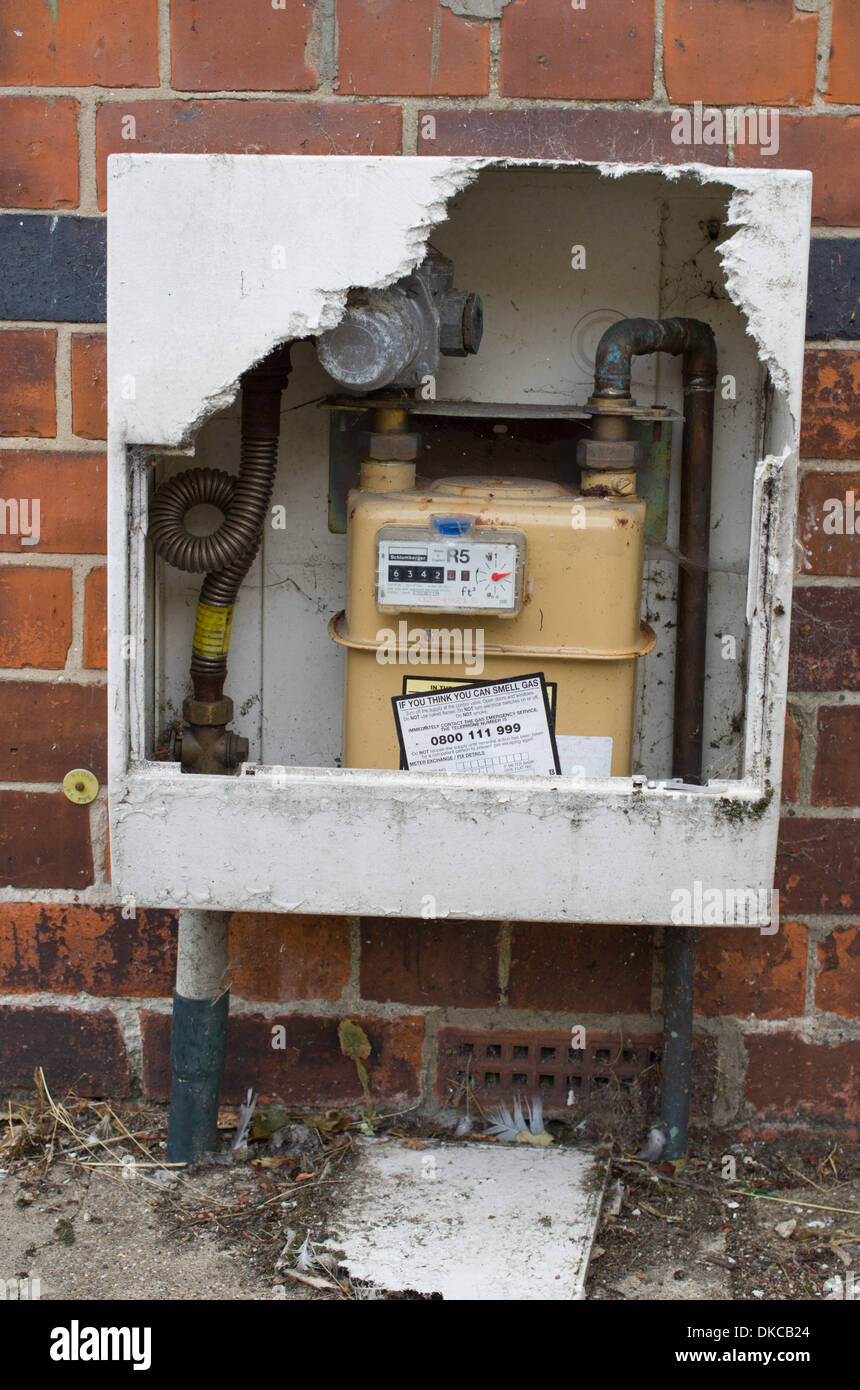 Fibreglass housing of gas meter broken exposing meter - Stock Image
