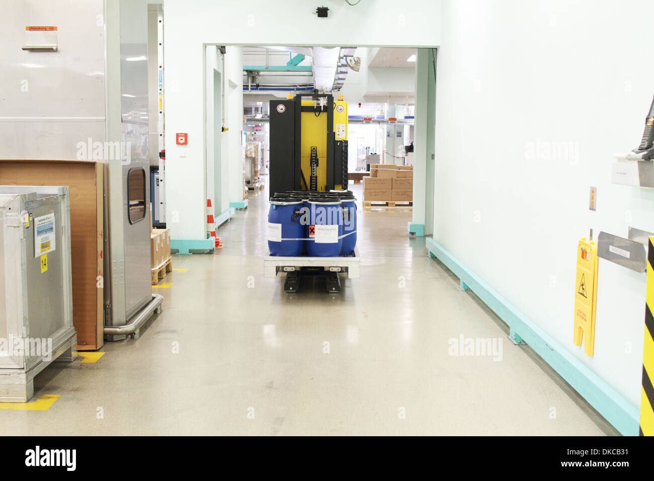 A self-acting fourwheel lifting truck carrying barrels with chemicals in an industrial hall of pharmacy. - Stock Image