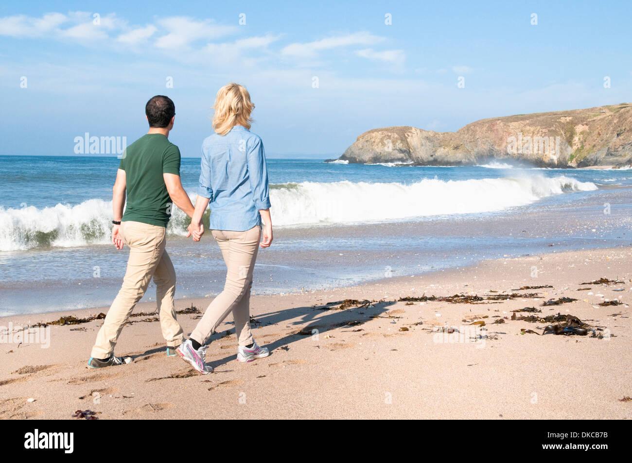 Mid adult couple walking on beach, Thurlestone, Devon, UK - Stock Image
