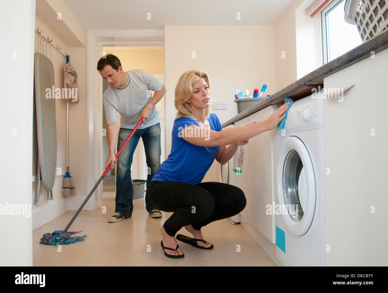 Mid adult couple cleaning kitchen in new home - Stock Image