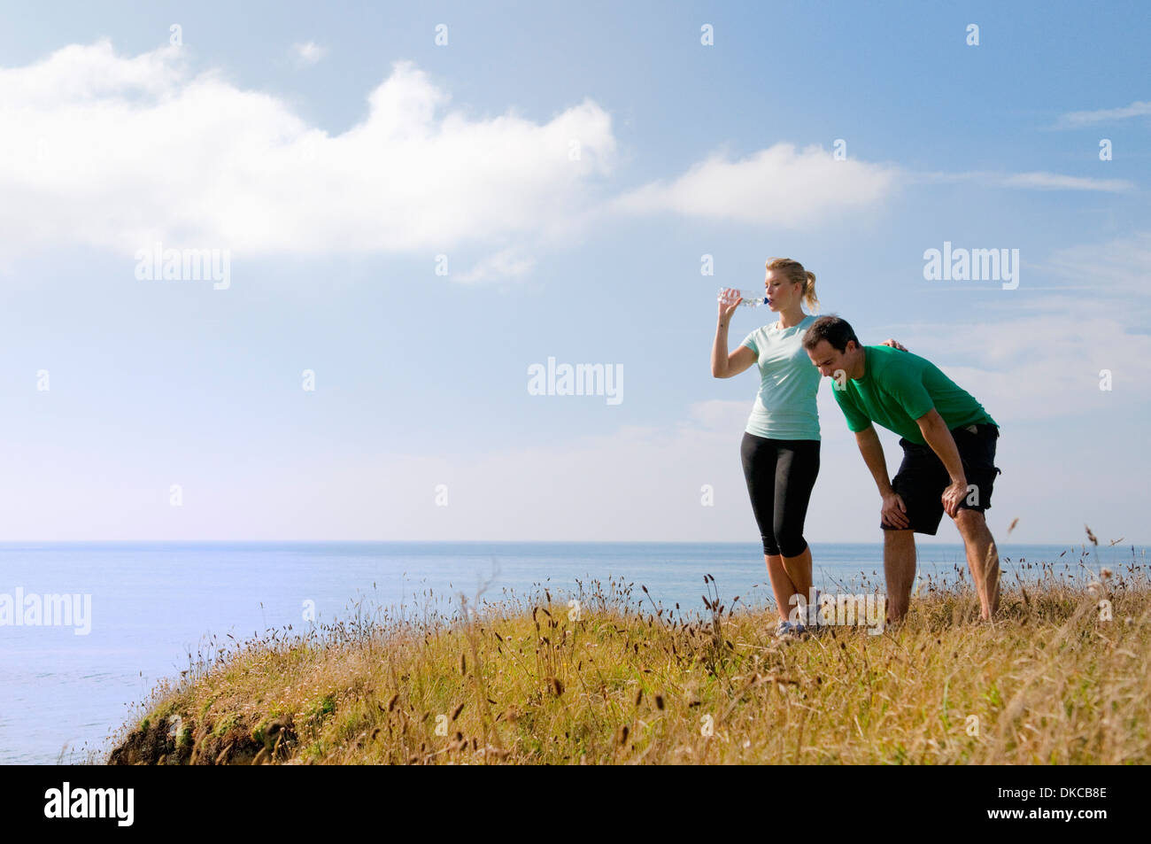 Mid adult couple resting from exercise, Thurlestone, Devon, UK - Stock Image
