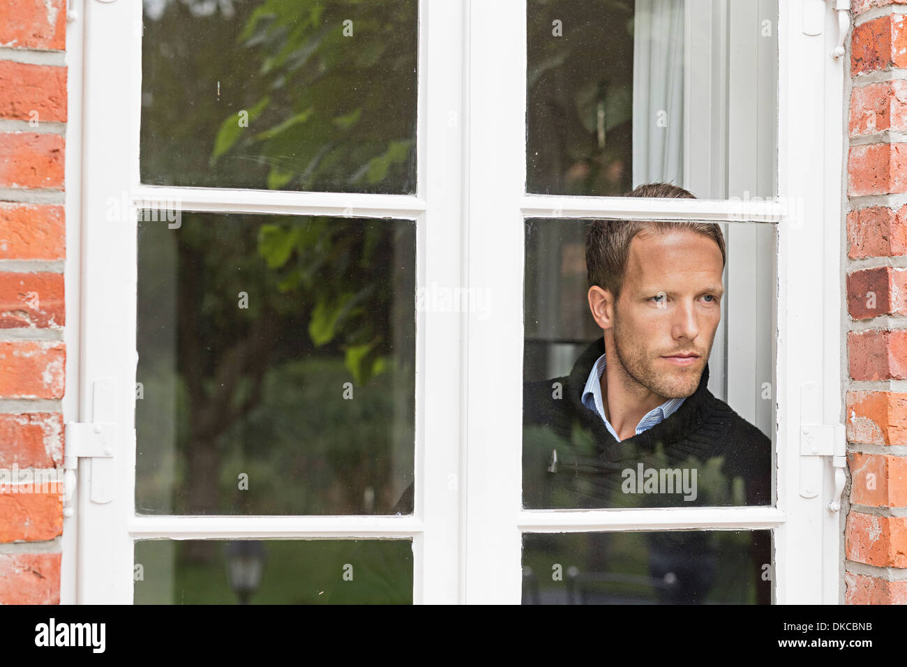 Mid adult man looking out of window - Stock Image