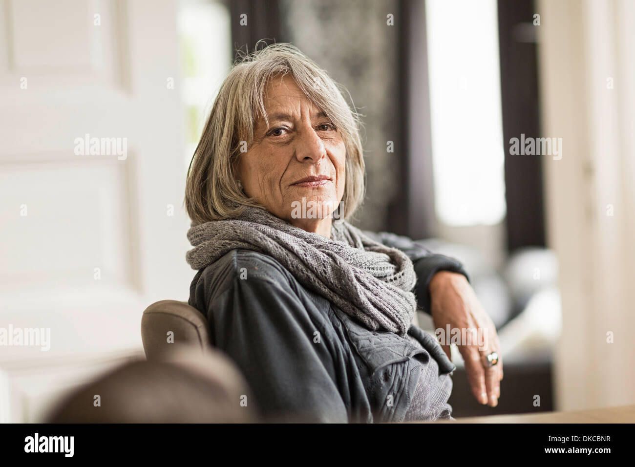 Portrait of senior woman with grey hair wearing scarf - Stock Image