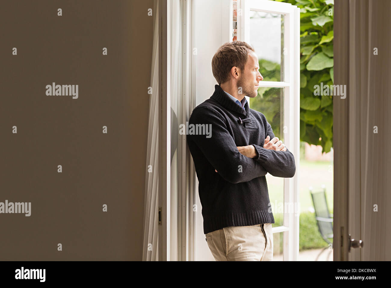 Mid adult man looking out of window, arms folded - Stock Image