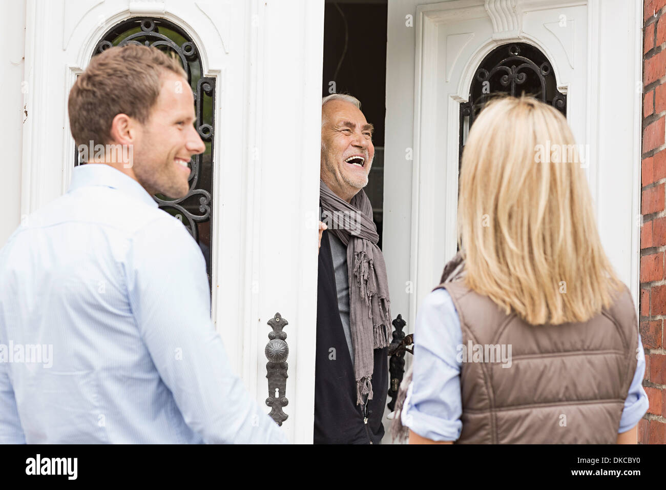 Father opening front door laughing - Stock Image