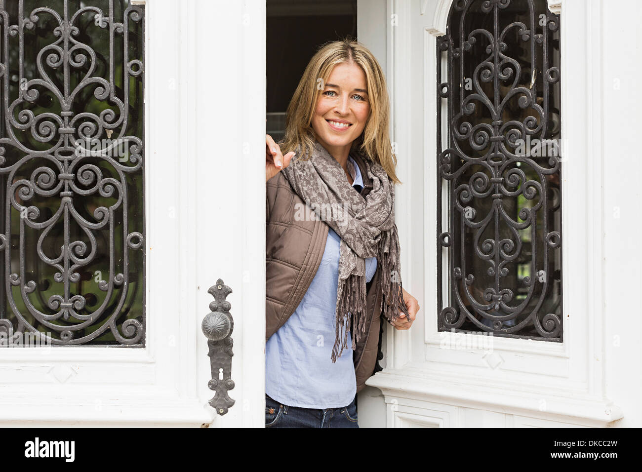 Mid adult woman opening front door - Stock Image