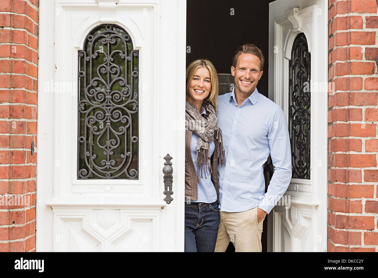 Mid adult couple by front door - Stock Image