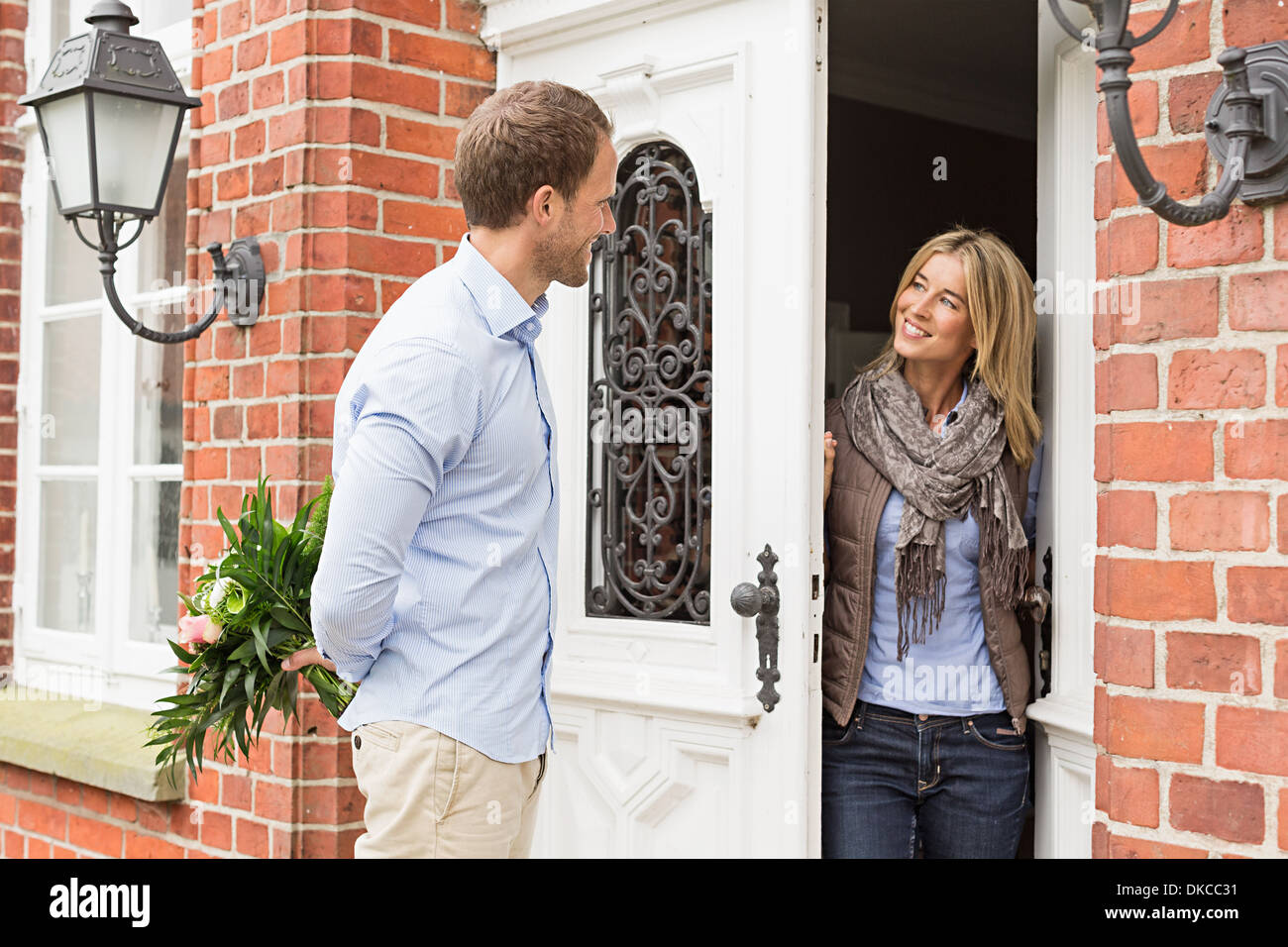 Mid adult couple, woman opening front door - Stock Image