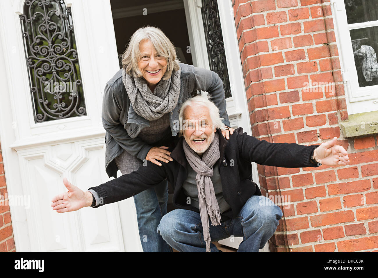 Senior couple by front door, man crouching with open arms - Stock Image