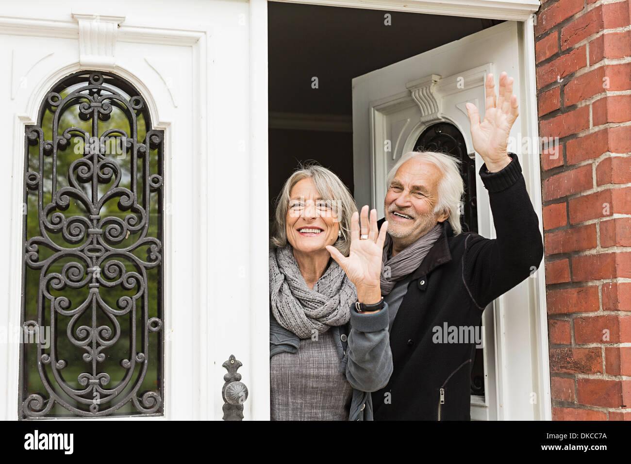 Senior couple waving by front door - Stock Image