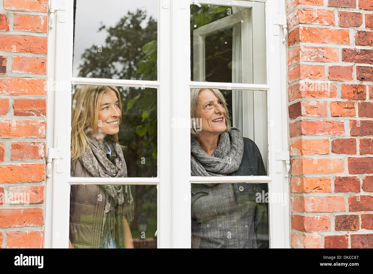 Mother and daughter looking through window - Stock Image