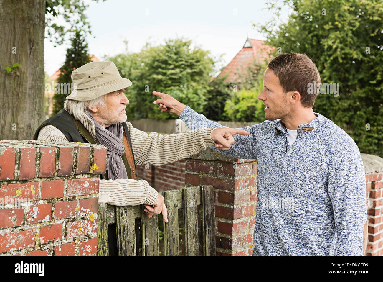 Senior man and mid adult man arguing - Stock Image