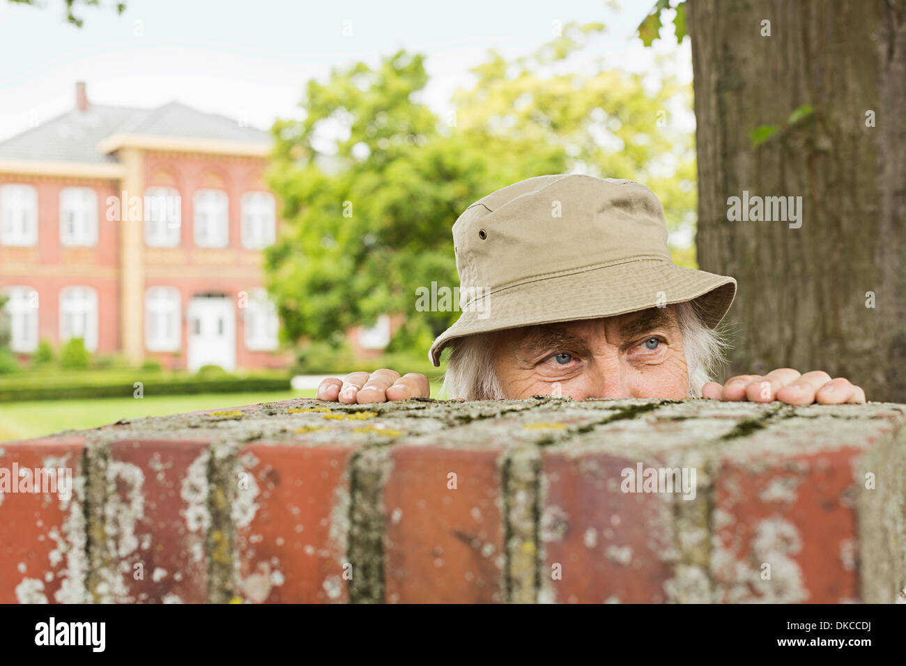 Senior man wearing hat peering over garden wall - Stock Image
