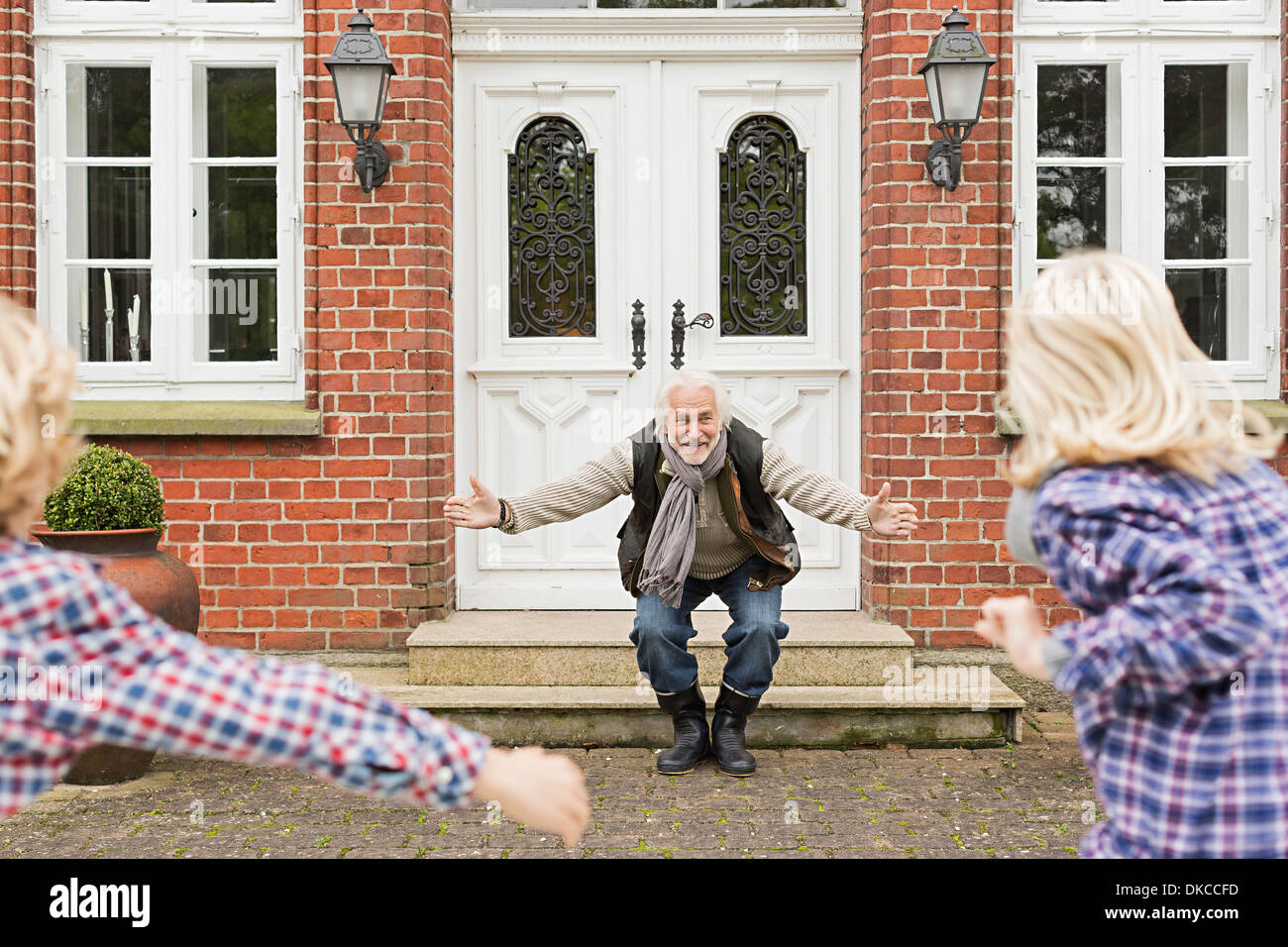 Grandfather welcoming grandchildren with arms open - Stock Image