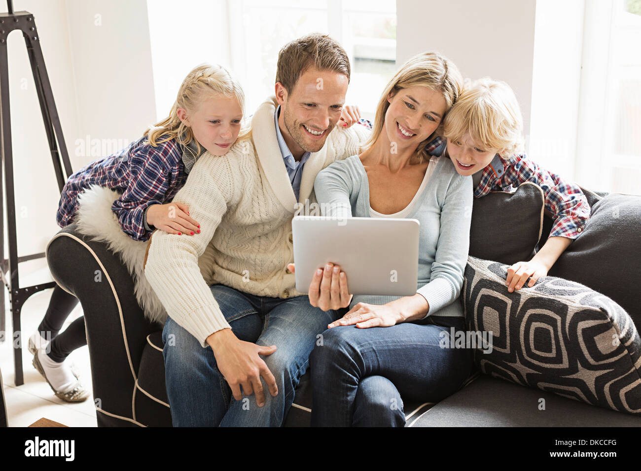 Parents with two children using digital tablet - Stock Image