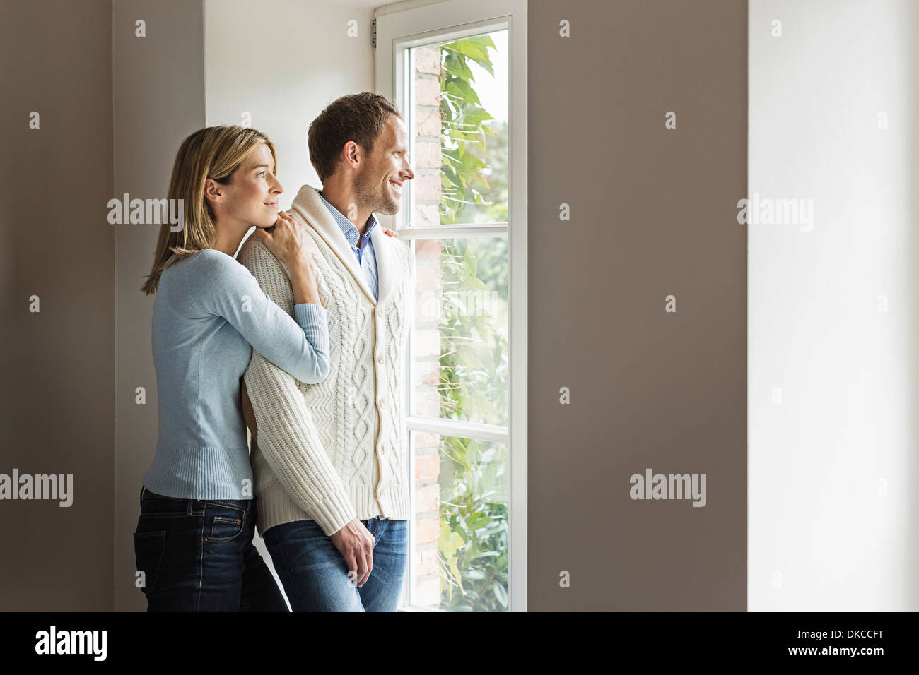 Portrait of mid adult couple looking out of window - Stock Image
