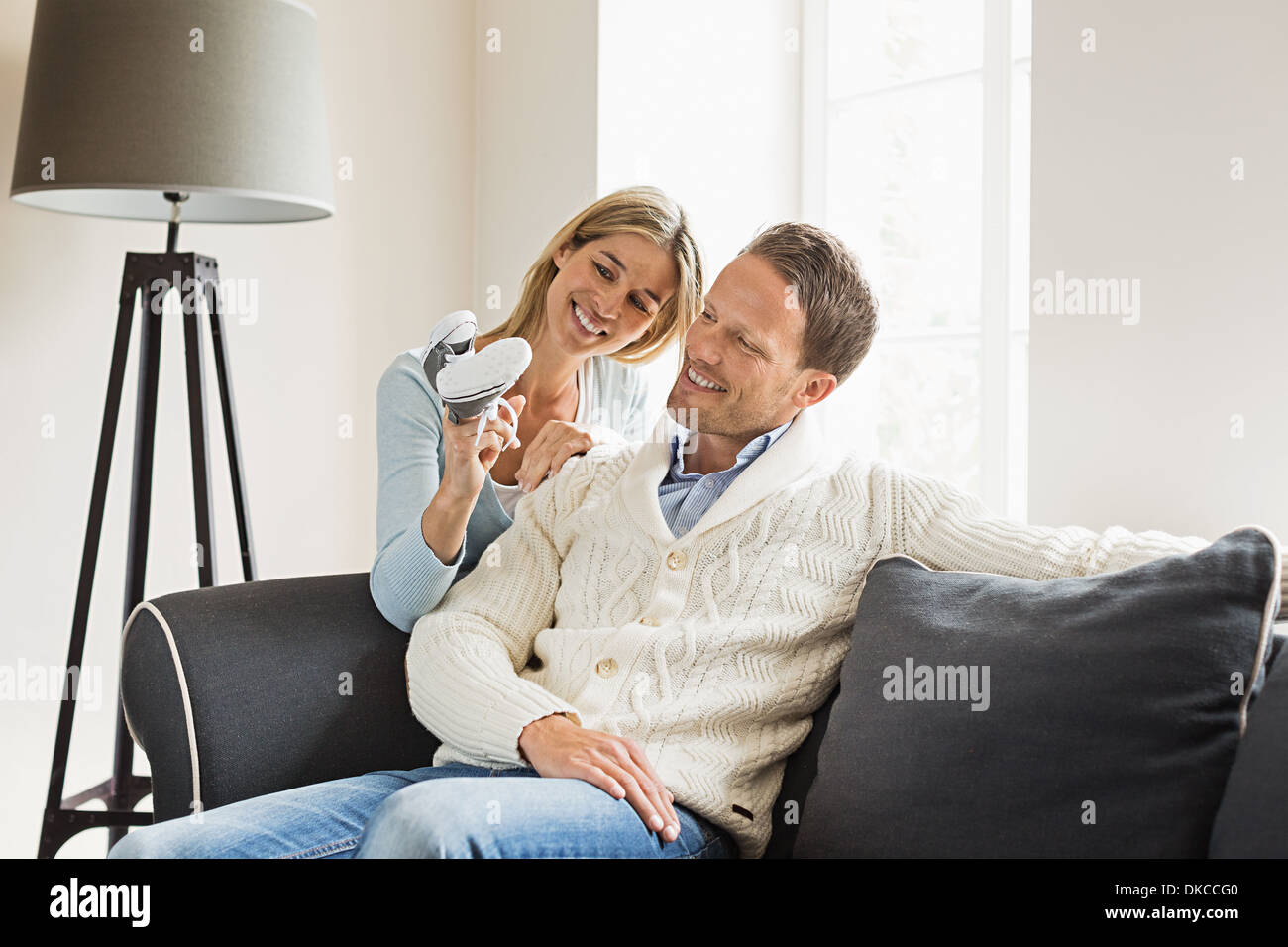 Mid adult couple, woman holding baby shoes - Stock Image